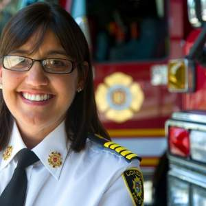Headshot of Chief Lori Hamer standing beside fire engine